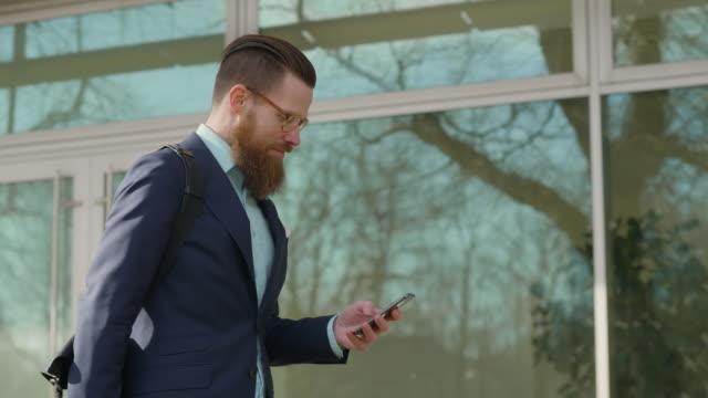 stockvideo's en b-roll-footage met zakenman die zijn slimme telefoon gebruikt terwijl het lopen in de stad - hipster persoon
