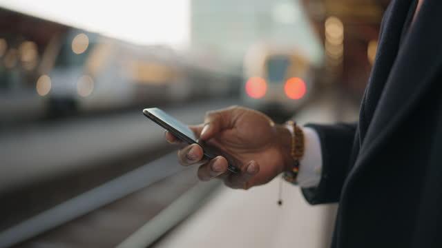 affärsman använder sin smartphone på tågstationen - sedd från sidan bildbanksvideor och videomaterial från bakom kulisserna