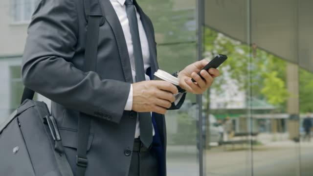 stockvideo's en b-roll-footage met slo mo zakenman die zijn smartphone gebruikt terwijl het drinken van koffie buiten het bureau - mid volwassen mannen