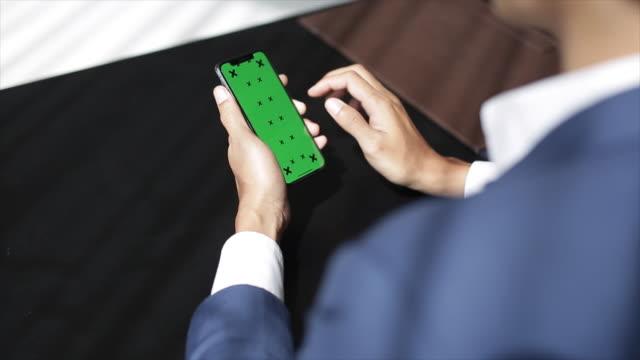 geschäftsmann mit iphone 10 green-screen - über die schulter stock-videos und b-roll-filmmaterial