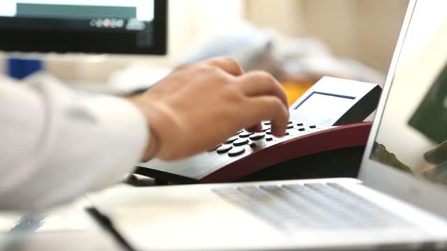 Businessman using landline phone and laptop