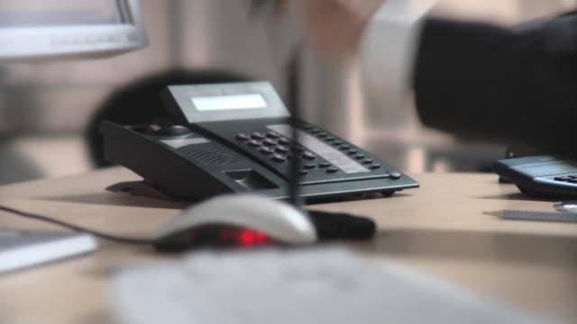 cu, selective focus, businessman using landline phone at desk, close-up of hand, berlin, germany - festnetzanschluss stock-videos und b-roll-filmmaterial