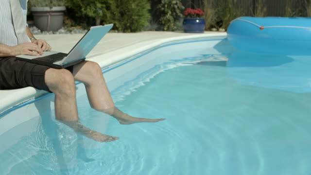 hd: businessman using laptop by the pool - bassängkant bildbanksvideor och videomaterial från bakom kulisserna
