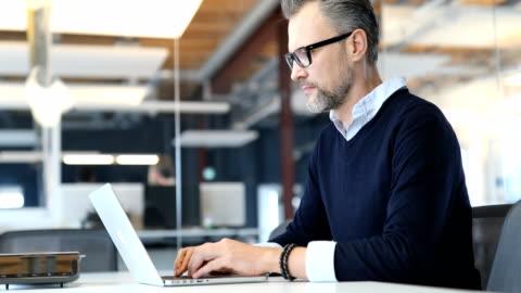 geschäftsmann mit laptop-computer im neuen büro - männer stock-videos und b-roll-filmmaterial