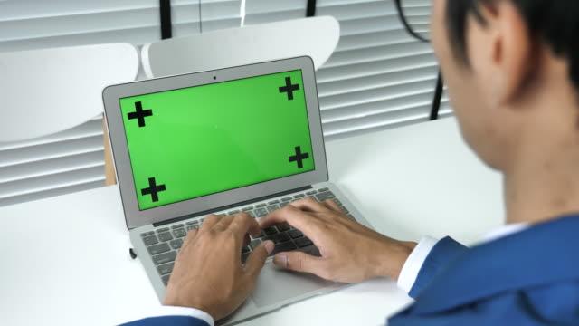 Businessman using Laptop Green screen in Office
