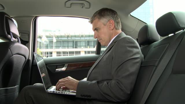 Businessman using laptop in car