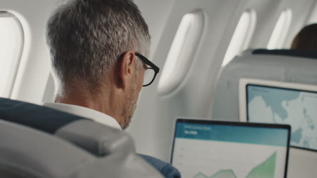 vidéos et rushes de homme d'affaires utilisant l'ordinateur portatif dans le jet d'entreprise - main au menton