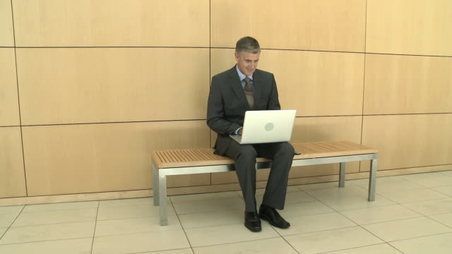 businessman using laptop in corridor - ベンチ点の映像素材/bロール