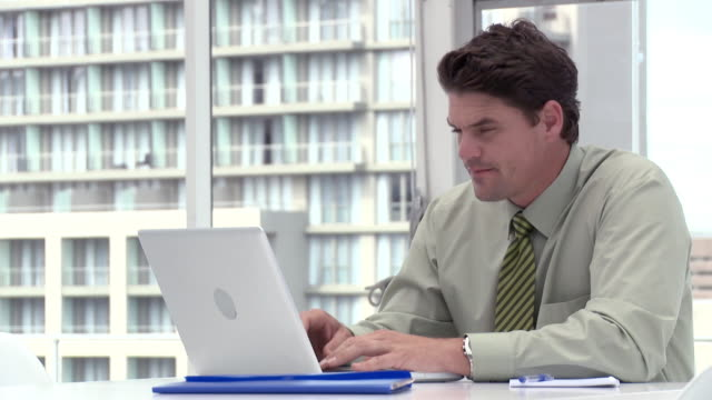 Businessman using laptop in office, looking up