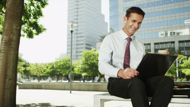 vídeos de stock e filmes b-roll de ms ds of businessman using laptop outdoors - camisa e gravata