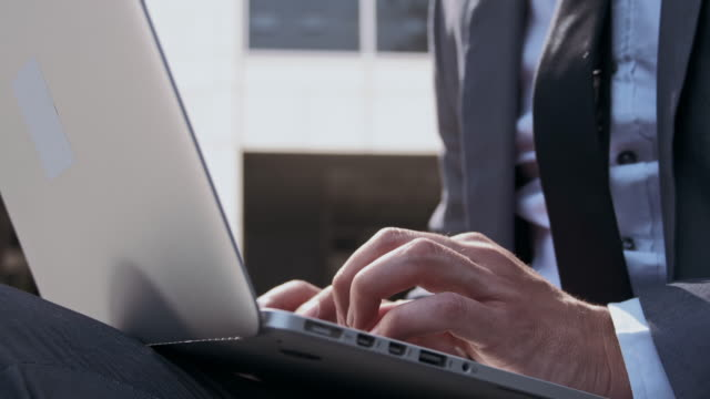 affärsman med laptop utomhus - använda en laptop bildbanksvideor och videomaterial från bakom kulisserna