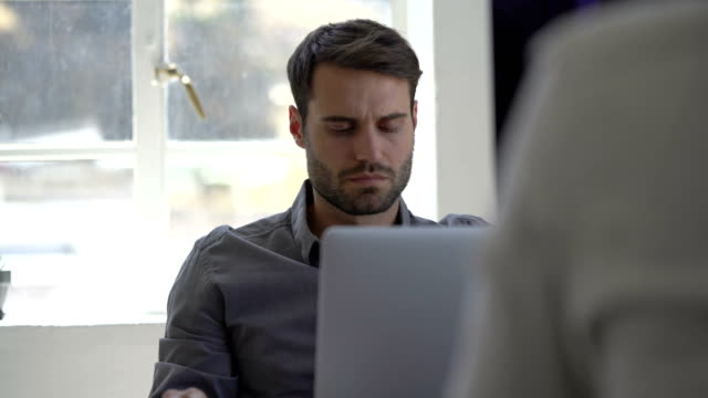 Businessman using laptop while talking in office