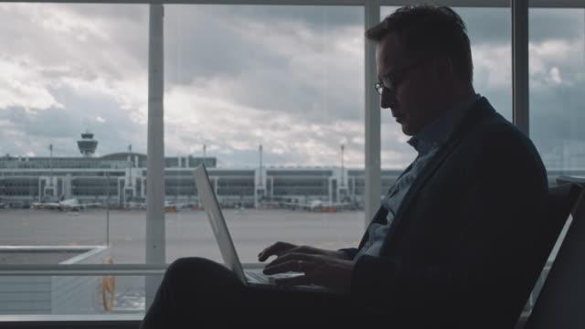 geschäftsmann mit laptop während der wartezeit am flughafen - geschäftsreise stock-videos und b-roll-filmmaterial