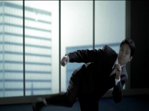 vidéos et rushes de businessman using martial arts expertise to kick and punch - karaté