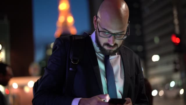 businessman using mobile at night - completely bald stock videos and b-roll footage
