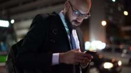 Businessman using mobile at night