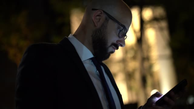 businessman using mobile at night - completely bald stock videos & royalty-free footage
