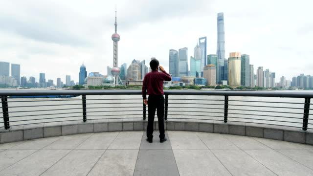 上海のスカイラインに対して携帯電話を使用するビジネスマン - full length点の映像素材/bロール