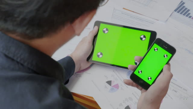 Businessman using mobile phone and digital tablet,Green screen