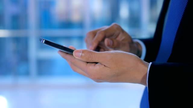 businessman using mobile phone at office - skjorta och slips bildbanksvideor och videomaterial från bakom kulisserna