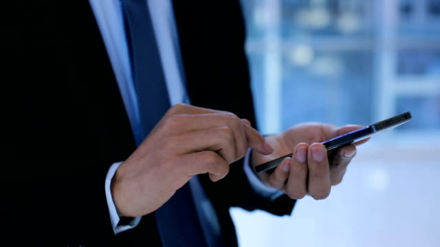 vídeos de stock, filmes e b-roll de businessman using mobile phone at office - traje completo