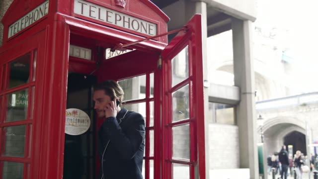ds businessman using mobile phone in the red telephone booth - public phone stock videos & royalty-free footage