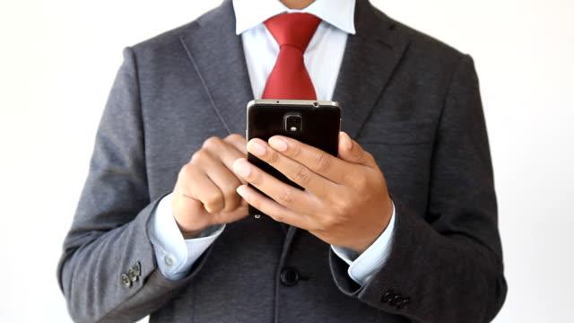 vídeos de stock, filmes e b-roll de empresário com o celular digitar texto - gravata
