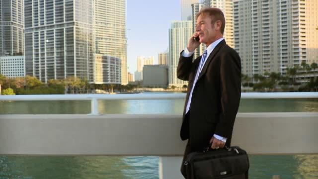 MS PAN SLO MO Businessman using mobile phone while walking / Miami Beach, Florida, USA