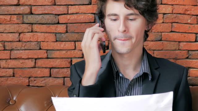 stockvideo's en b-roll-footage met businessman using mobile phone,dolly shot - financiële pagina