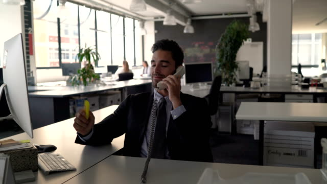 Businessman using  phone and computer at desk
