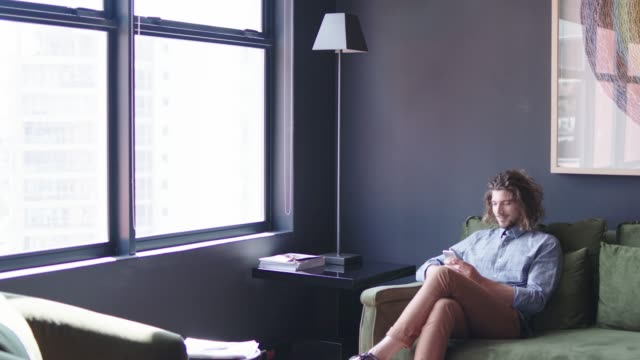 businessman using phone and looking towards window - person sitting cross legged stock videos & royalty-free footage