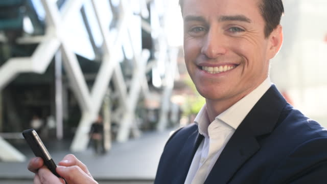 Businessman using phone and smiling to camera