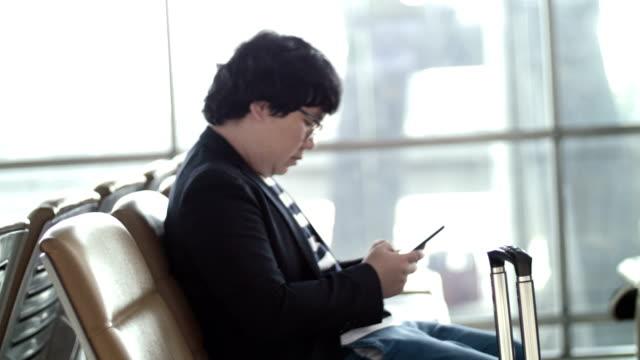 Homme d'affaires à l'aide de téléphone à l'aéroport