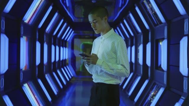 vídeos y material grabado en eventos de stock de businessman using phone in spaceship corridor - pasillo característica de edificio