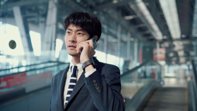 businessman using phone on escalator at airport - full suit stock videos & royalty-free footage