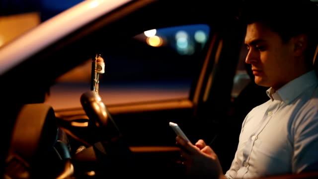 vidéos et rushes de homme d'affaires utilisant le téléphone - parking