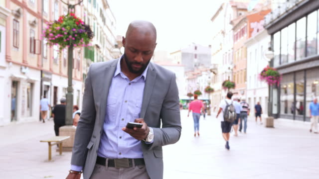 businessman using smart phone - 4k video - on the move stock videos & royalty-free footage