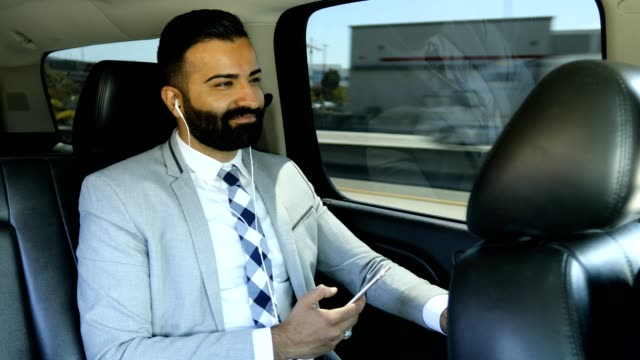 Businessman Using Smart Phone in a Limousine