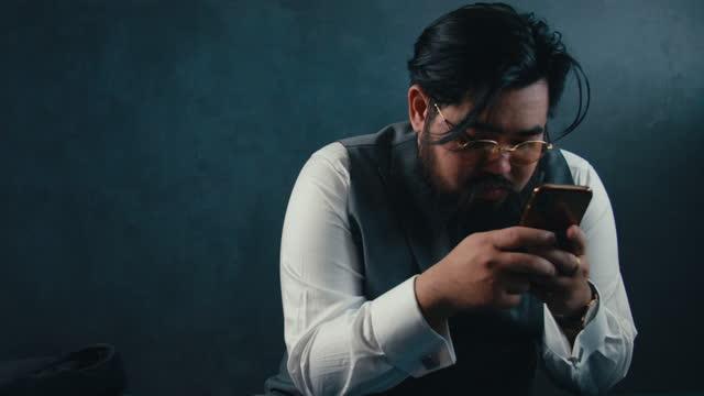 vídeos de stock e filmes b-roll de businessman using smart phone on black background - vestuário de trabalho formal
