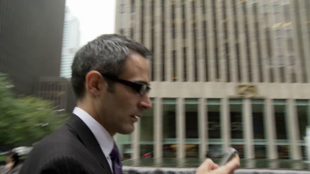 CU SHAKY Businessman using smart phone on busy street / New York City, New York, USA
