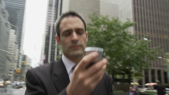 CU SHAKY Businessman using smart phone on busy street / New York City, New York, USA