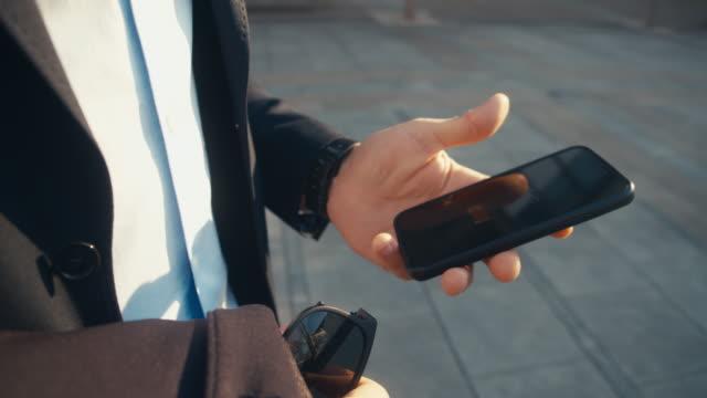 vídeos de stock, filmes e b-roll de slo mo ms zo empresário usando telefone inteligente na rua - send