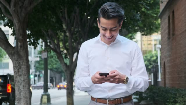 Businessman using smart phone outdoors on the street