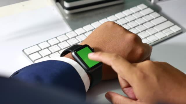 Businessman using smart watch, Green screen
