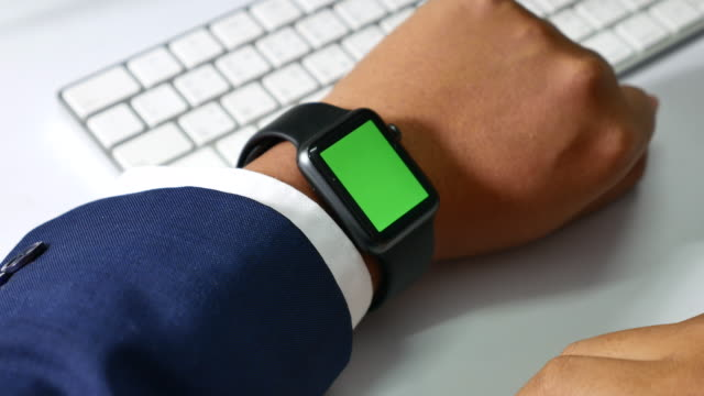 Businessman using smart watch in the office, Green screen