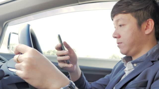 ビジネスマンはスマートフォンを使用してお車のクローズアップ - 不注意点の映像素材/bロール