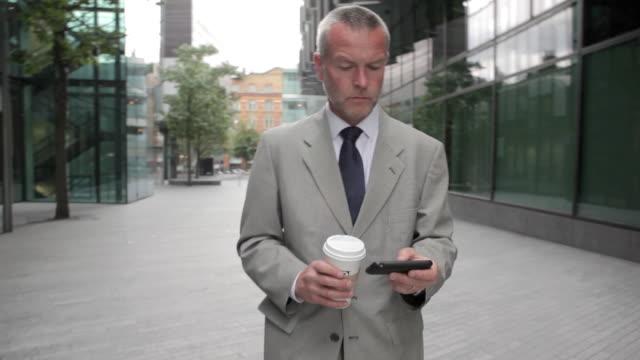 businessman using smartphone in city street - archivista video stock e b–roll