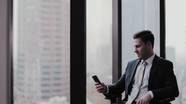businessman using smartphone in office skyscraper - ペントハウス点の映像素材/bロール