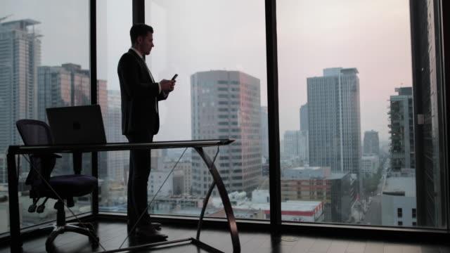 vídeos de stock e filmes b-roll de businessman using smartphone in skyscraper office - negociante ocupação financeira
