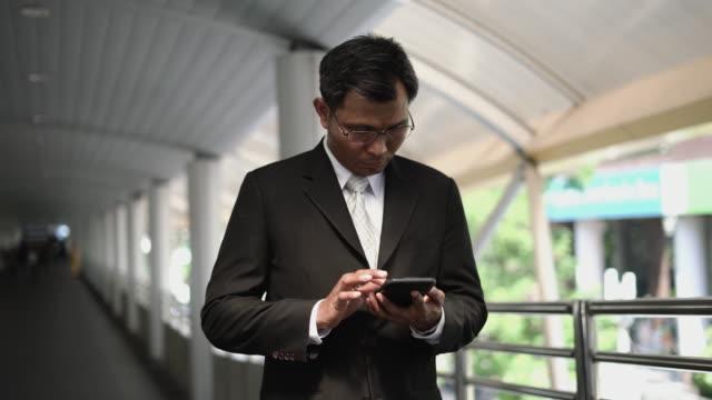 vídeos de stock e filmes b-roll de businessman using smartphone. - camisa e gravata